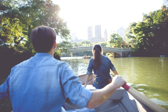 Couple have fun outdoor rowing boat on lake at Central park, New York