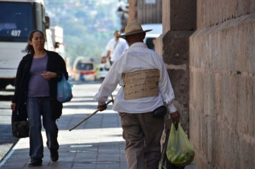 A viejo with a sign on his back asking for help