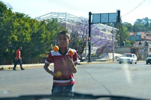 Street kid juggling oranges