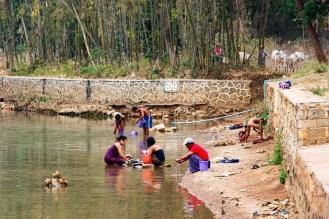 Frauen waschen Klammotten im Indein Dorf