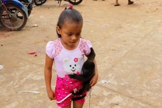 Mädchen mit kleinem Affe als Haustier in Peru