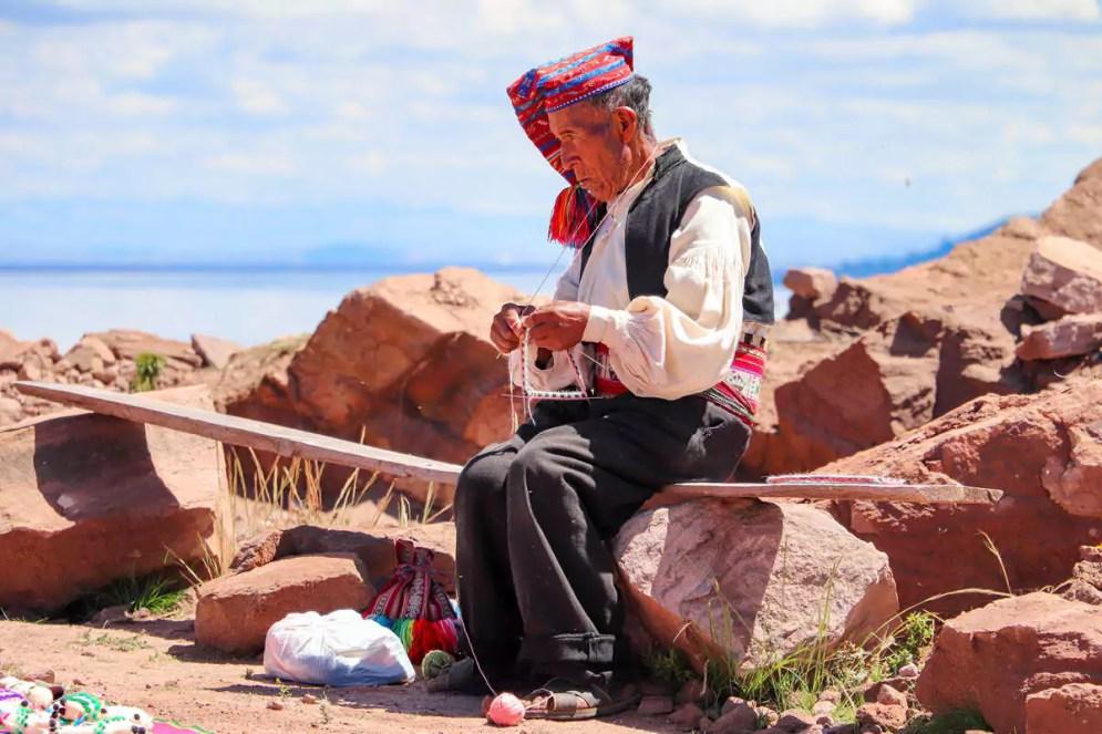 Quechua Mann strickt auf Taquile