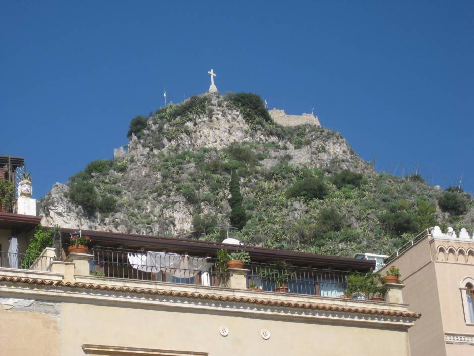 The cross of the church of Madonna della Rocca can be seen from the town of Taormina below.