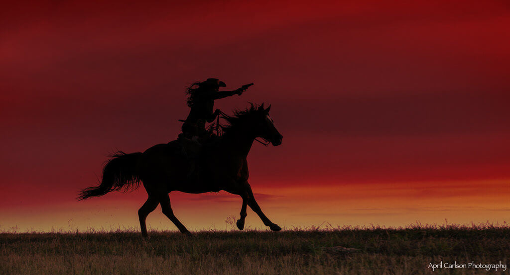 Horse Photography Workshop: Silhouette of cowgirl with a gun on her horse