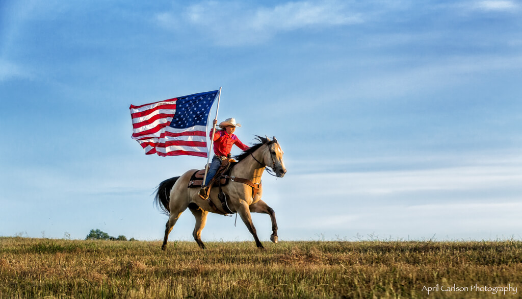 Horse Photography Workshop: Buckskin horse with cowgirl riding and the American flag waving in the breeze