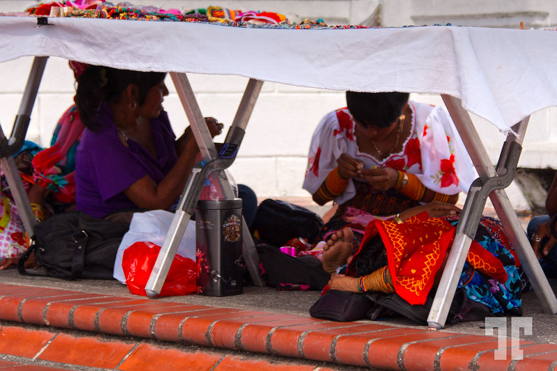 Kuna vendors hiding from the sun in Casco Viejo Panama, while working on their crafts