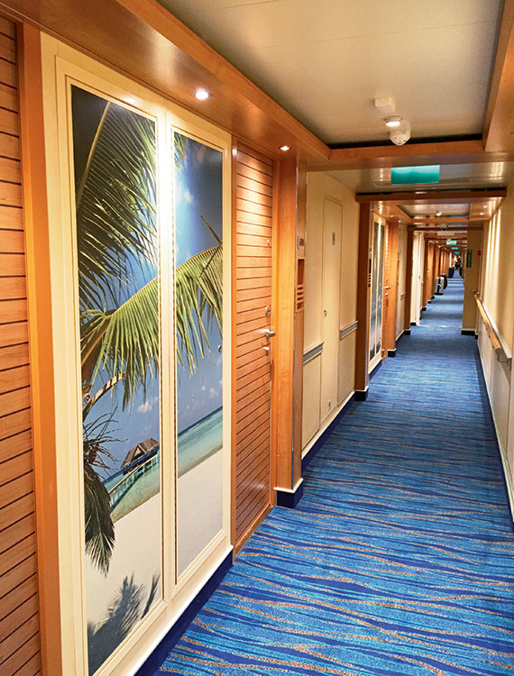 The stateroom corridors on Carnival Vista feature floor-to-ceiling photo panels. Photo Credit: Tom Stieghorst