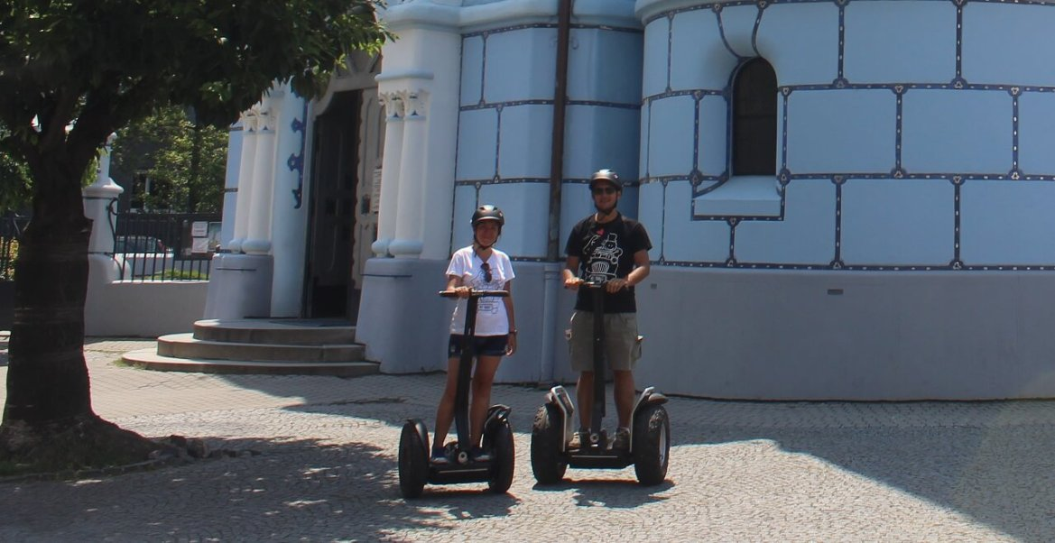 On Segway in front of the blue church