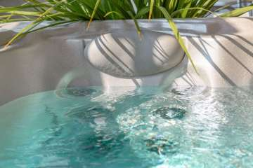 hot tub with decorative plants evoking a calm and relaxed atmosphere