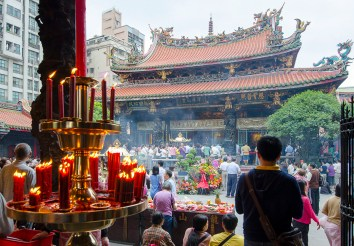 Worshippers jam the interior of the Longshan Temple in one of the oldest sections of Taipei, lighting candles and incense, bringing food, clothes and other offerings for the temple's gods.