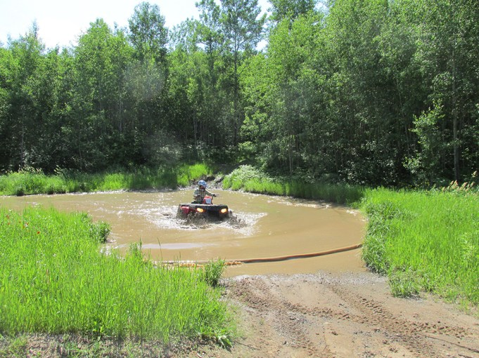 Linda Aksomitis driving her ATV through the mud hole. Photo Credit: Mike Terrell
