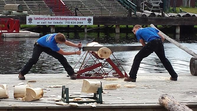 Lumberjacks using a buck saw. Photo Credit: Linda Askomitis