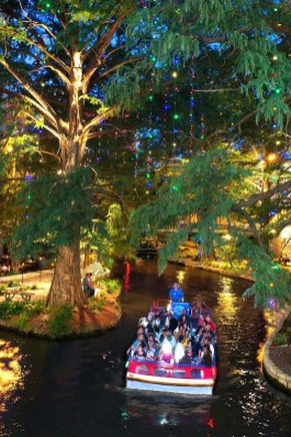 A holiday river barge floating along the River Walk. Photo Credit: VisitSanAntonio.com