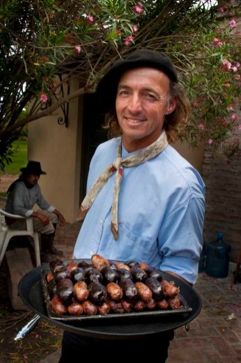 Gaucho serves a plate of sausages at San Antonio de Areco Ranch