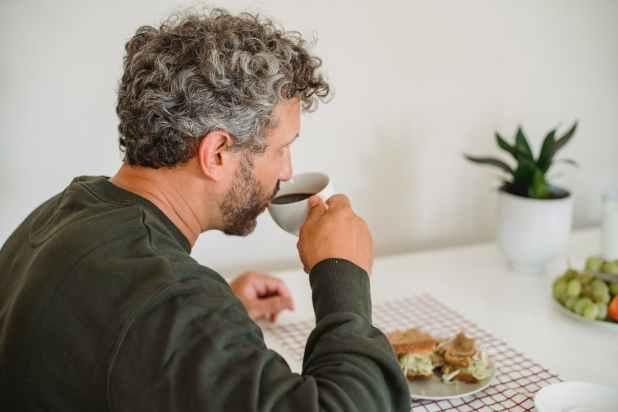 bearded man having breakfast in kitchen