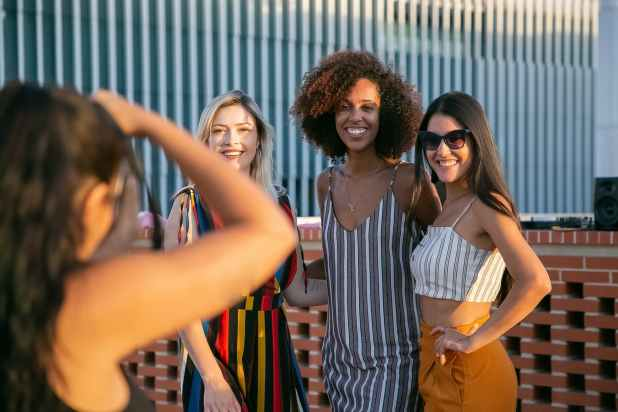 faceless woman taking photo of stylish female friends on terrace
