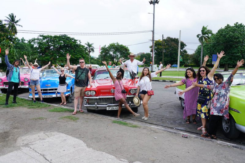 Group cheers in front of classic cars