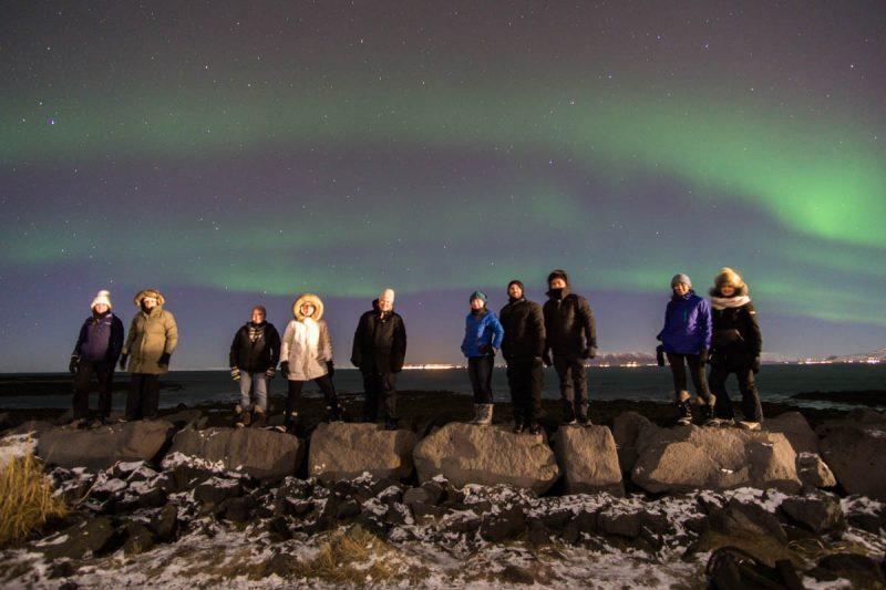 Group shot on rocks under Northern Lights