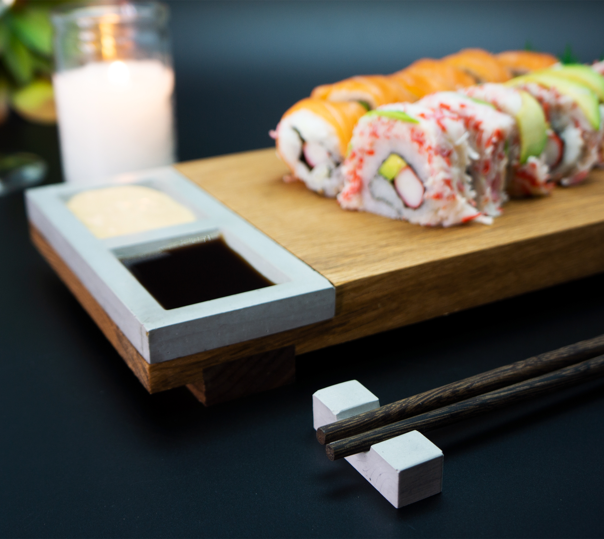 sushi board with concrete sauce tray holding spicy mayo and soy sauce
