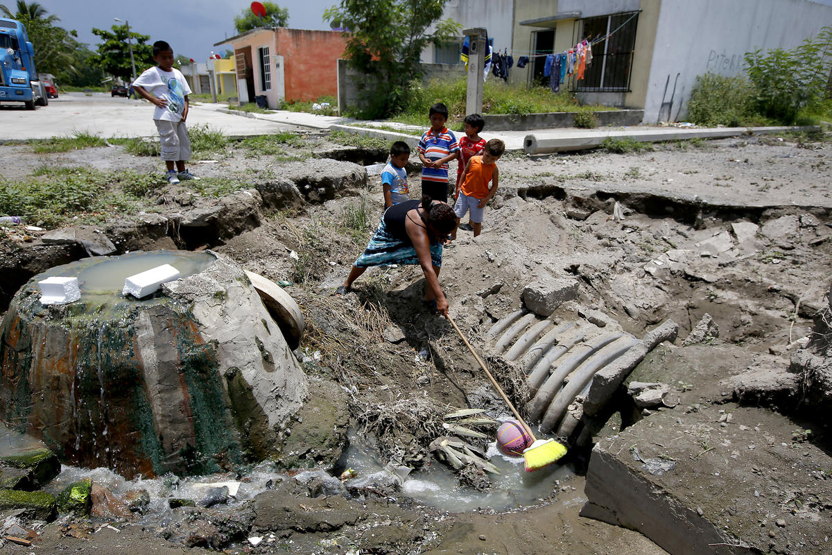 hight resolution of adela blanco uses a broom to retrieve a basketball from an open pit of raw sewage near her home in colinas de santa fe in veracruz mexico