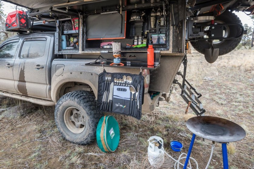 Alu-Cab camper door is open to show all the camp kitchen accessories.