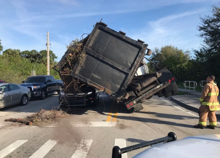"""Truck carrying """"drop off dumpster"""", flipped onto an SUV; no injuries reported"""