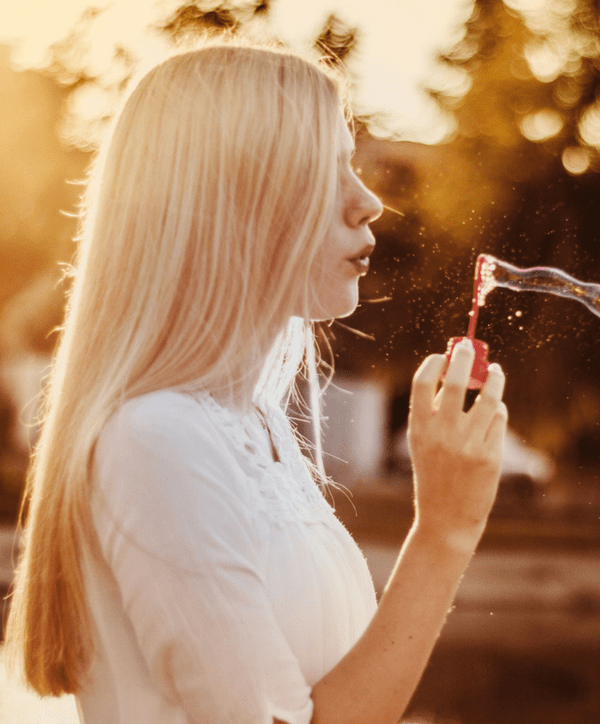 woman breathing out and blowing bubbles