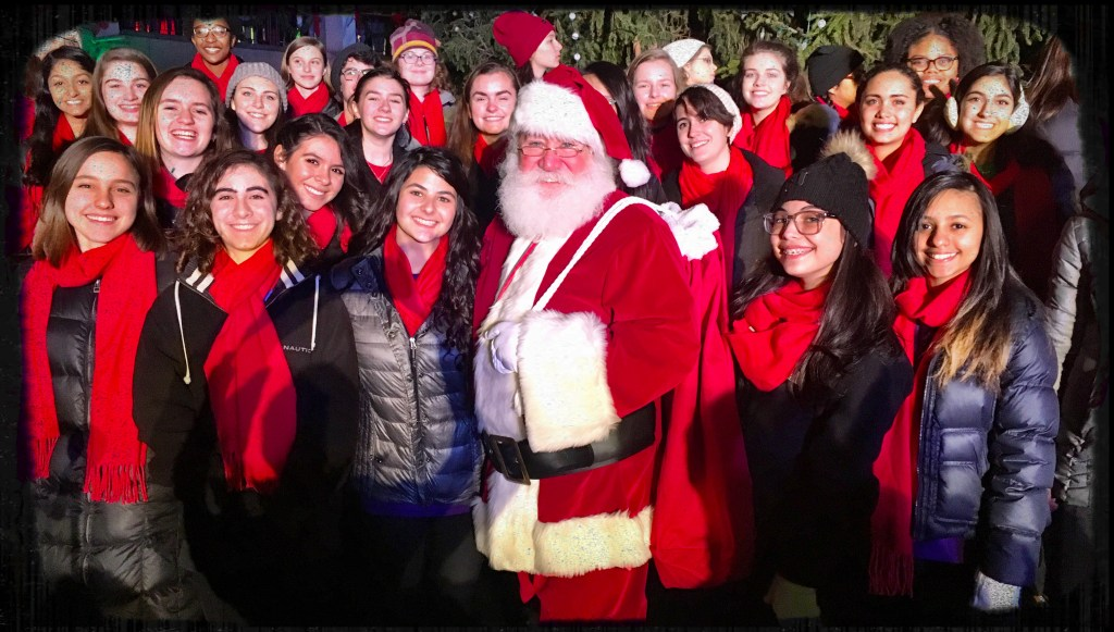 Santa Claus standing in front of the Boston Children's Chorus wearing red scarves.