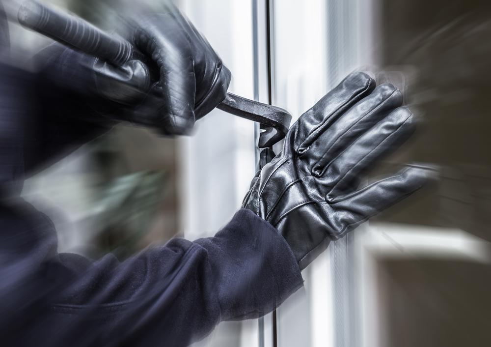 A burglar jimmies open a window