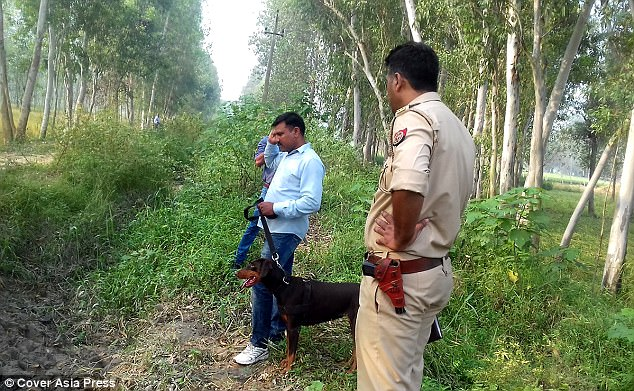 Policemen with sniffer dog searching for evidence near the spot where dead body of four-year-old girl Akshita was found near her house in Sahranpur area of Uttar Pradesh
