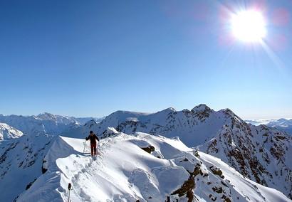 Ultimi passi alla Cima Riacci. Alle spalle dell'alpinista, il Pizzo Coppetto 3066 m.