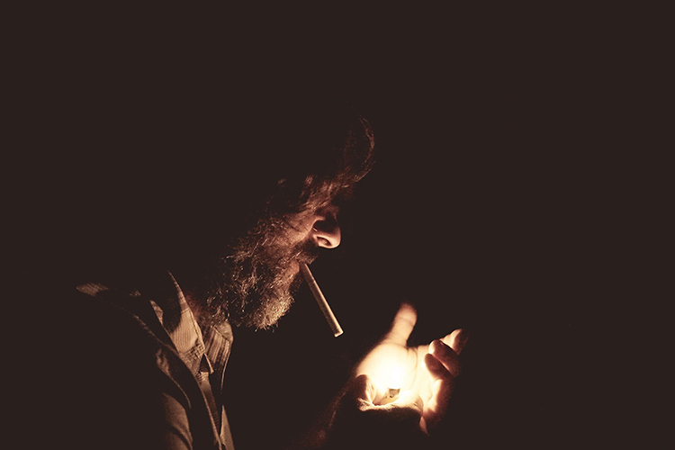 handsome man with beard smoking a cigarette