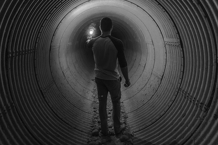 man standing in tunnel reaching for light