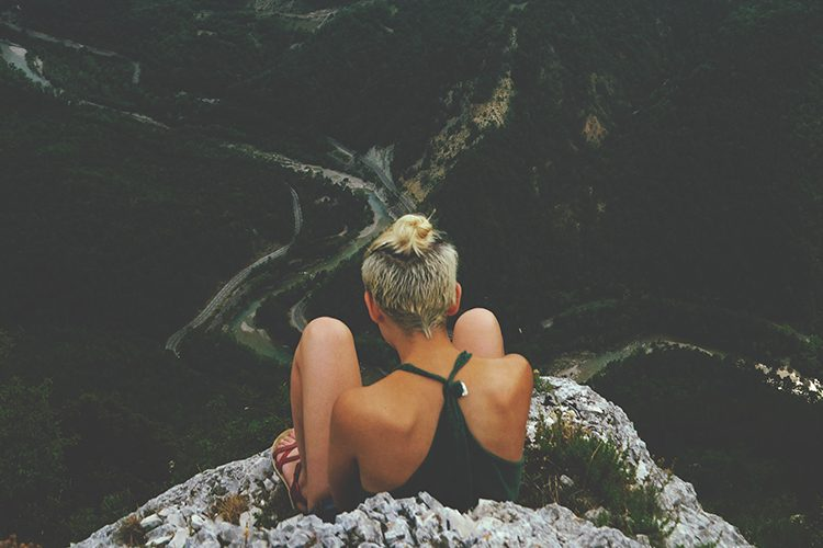 girl sitting on edge of mountain with a valley and river below