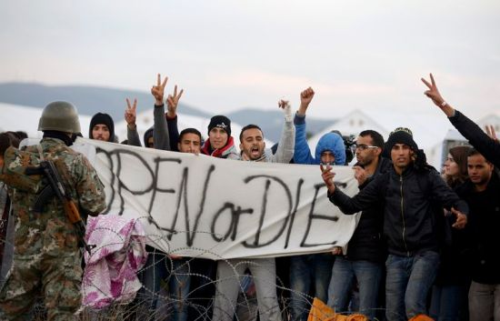 Migrants shout in front of a Macedonian police officer after trying to cross the border from Greece into Macedonia, near Gevgelija, Macedonia, November 26, 2015. Countries along the Balkan route taken by hundreds of thousands of migrants seeking refuge in western Europe last week began filtering the flow, granting passage only to those fleeing conflict in Syria, Iraq and Afghanistan.   REUTERS/Stoyan Nenov