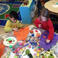 Decorating pizzeria aprons with vegetable toppings during Castle Week.
