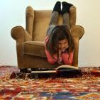 Nena llegint estirada a terra
