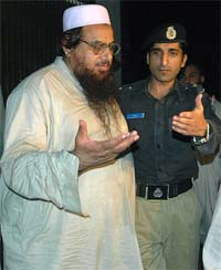 A Pakistani police officer escorts Hafiz Mohammad Saeed outside his residence in Lahore late on Monday night.