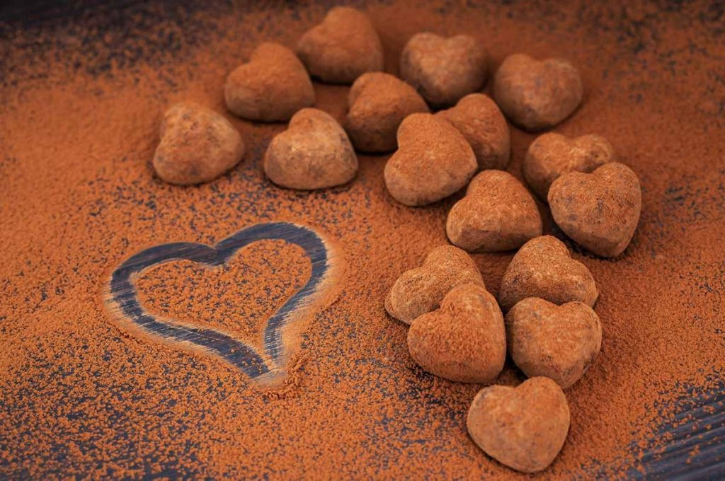 Heart shaped chocolate truffles on cocoa powdered table.