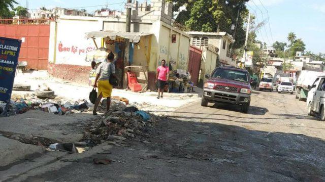 La route de Carrefour en mauvais état, infestée d'immondices