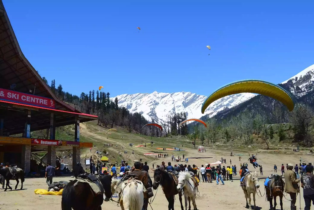 People paragliding down Solang Valley