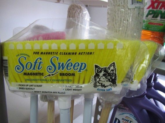 A cat drawing on a plastic wrap around a magnetic broom.