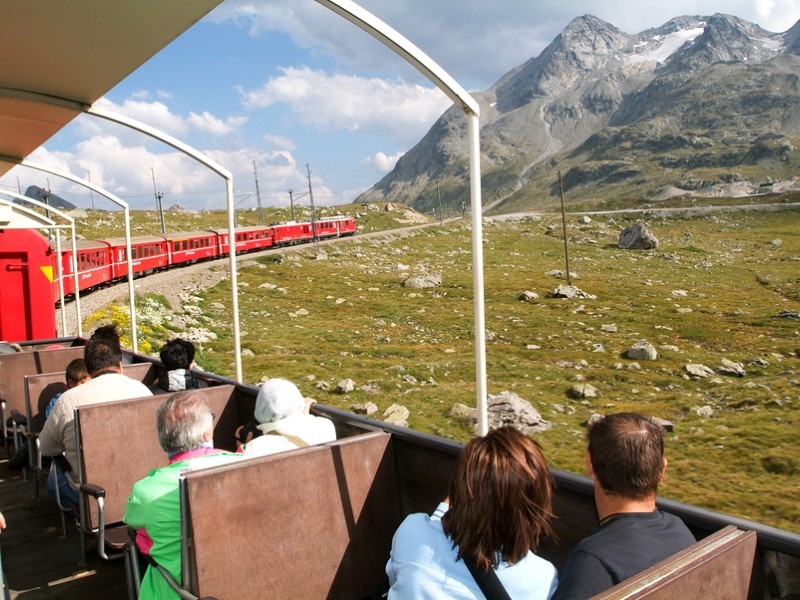 People sitting on the Bernina express train and admiring the scenic view on the Swiss alps