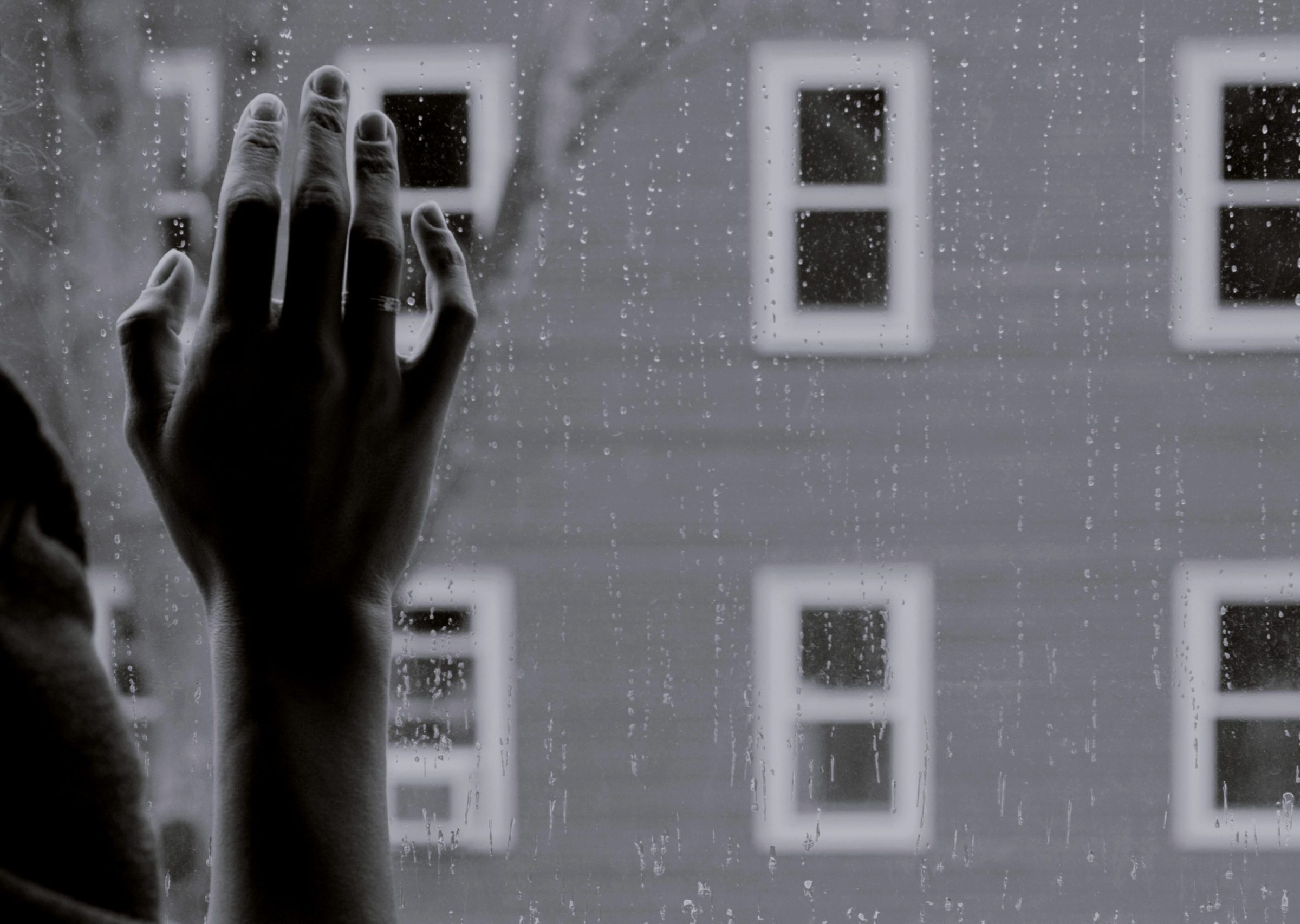 lonely hand against window pane during social distancing