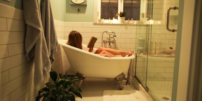 woman laying in old fashioned bathtub reading book while social distancing