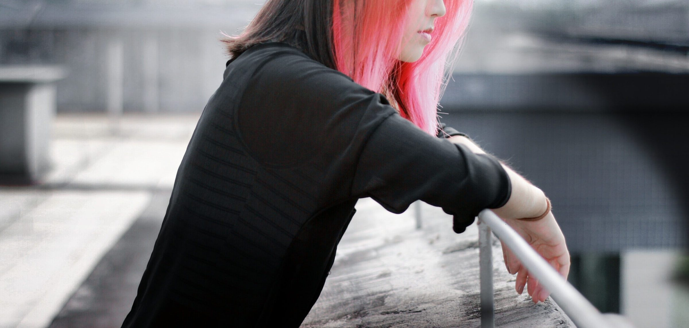 woman with pink hair leaning over railing