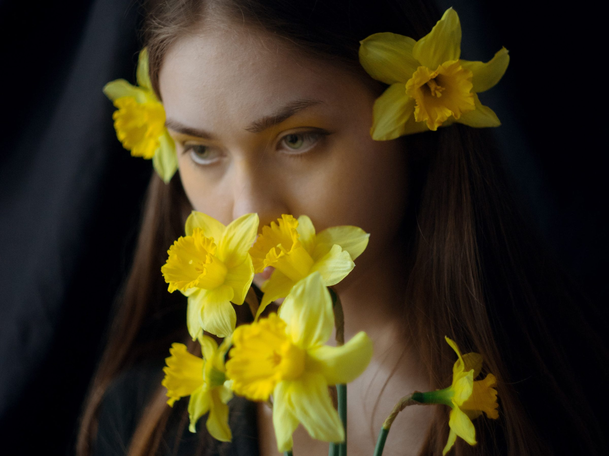 woman with flowers covering mouth, suggestive of not being heard, being silenced