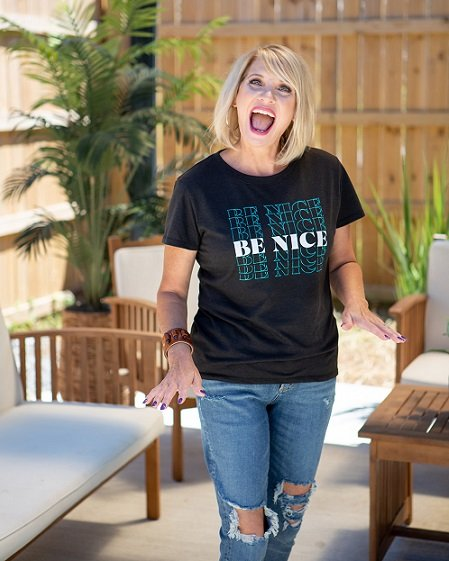 Trish McKinnley manifesting expert, wearing black t-shirts and jeans, smiling widely and looking happy