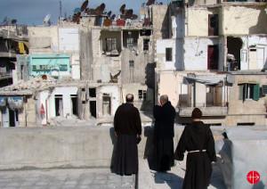 francescani davanti alle rovine