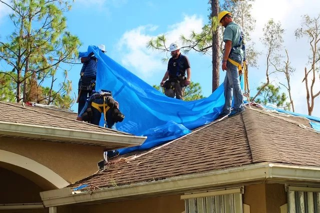 Roofing contractors of S & M Associates apply and affix FEMA supplied blue tarp sheets onto a local Naples, Florida home in order to provide a temporary solution for residence housing shelter and prevent further damage